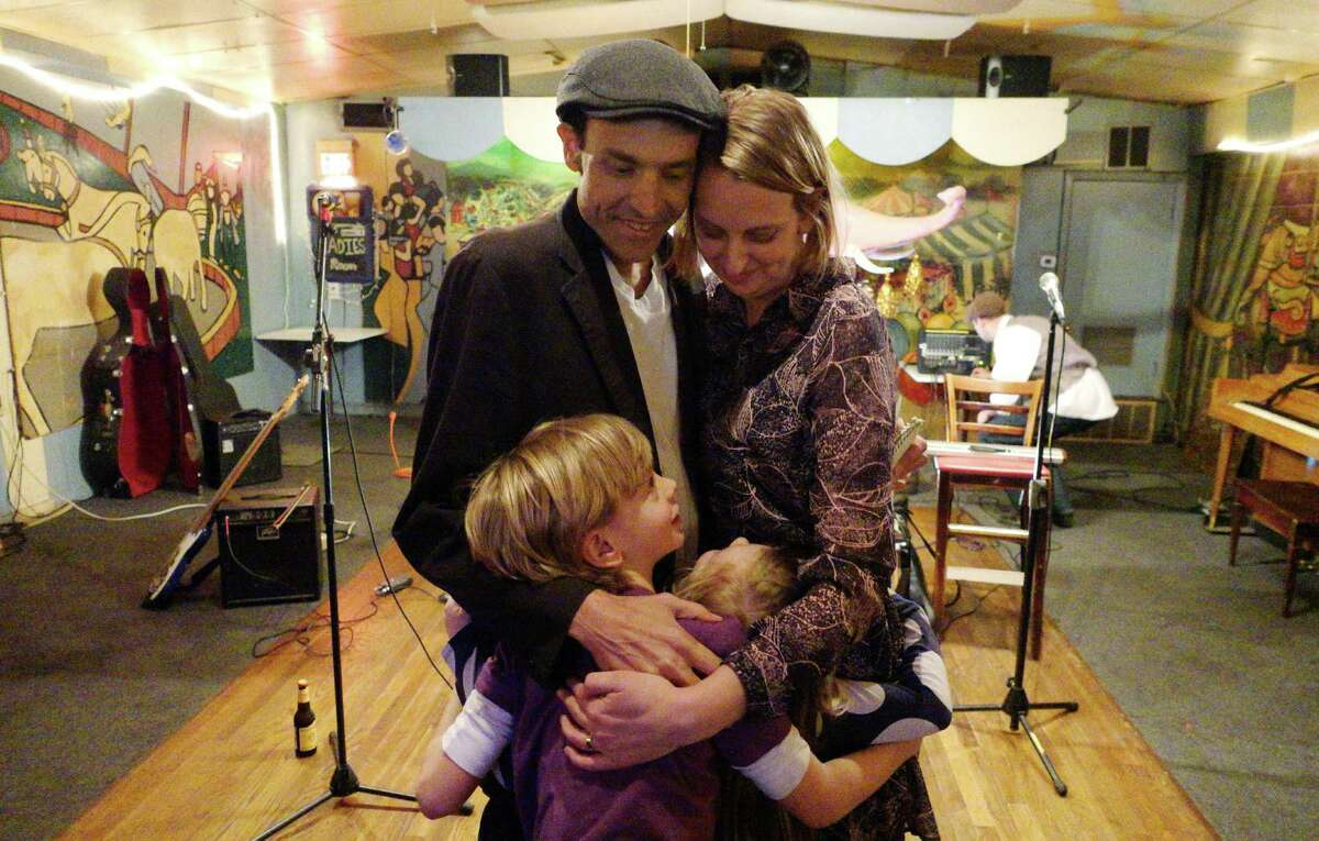 Michael Brick with his wife and children at a performance by his old band, the Music Grinders, in mid-January at the Carousel Lounge, in Austin.