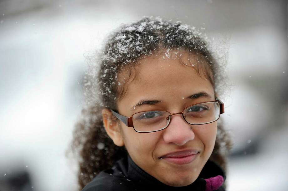 Angelica Nunez, 16, gets snow in her hair while waiting for her brother Mike, to clear off the car on Stephens Street in Danbury, Monday, Feb. 8, 2016. Photo: Carol Kaliff, Hearst Connecticut Media / The News-Times