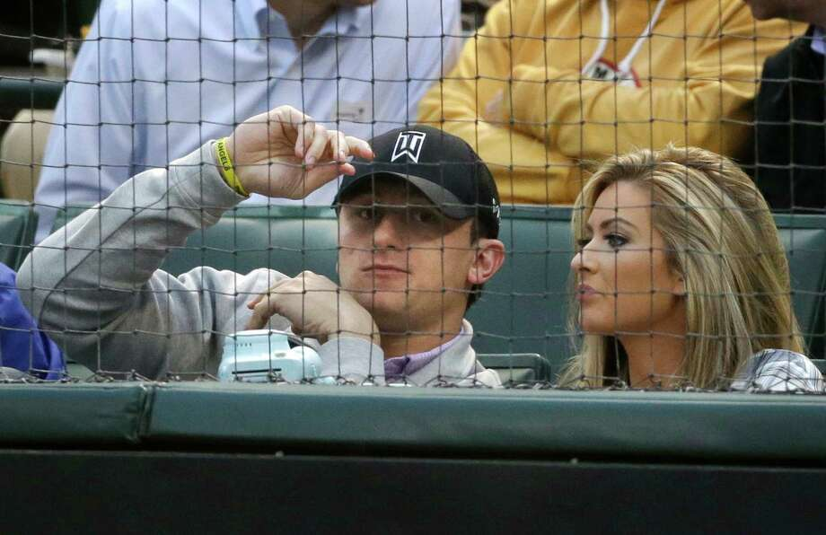 Johnny Manziel and ex-girlfriend Colleen Crowley take in a Texas Rangers game last year. In her affidavit seeking a protective order, Crowley claims Manziel held her against her will and hit her so hard she lost hearing in her left ear. Photo: LM Otero, Associated Press / AP