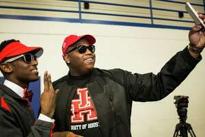 Bellaire's Courtney Lark, left, takes a photo with Lamar's Dixie Wooten III during the Houston Independent School District's National Signing Day ceremonies at the Mark Anthony Pavilion on Wednesday, Feb. 3, 2016, in Houston. Both signed a letter of intent to play football at the University of Houston.