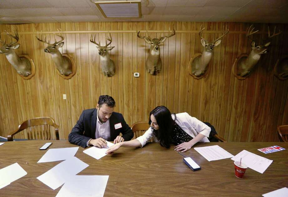 Cristina Covarrubias-Diaz leans over to help her husband Rogelio Diaz, Jr., as they open a phone bank at the Hillary Clinton campaign headquarters for the Houston area, Thursday, Feb. 4, 2016, in Houston. Photo: Jon Shapley, Houston Chronicle / © 2015  Houston Chronicle