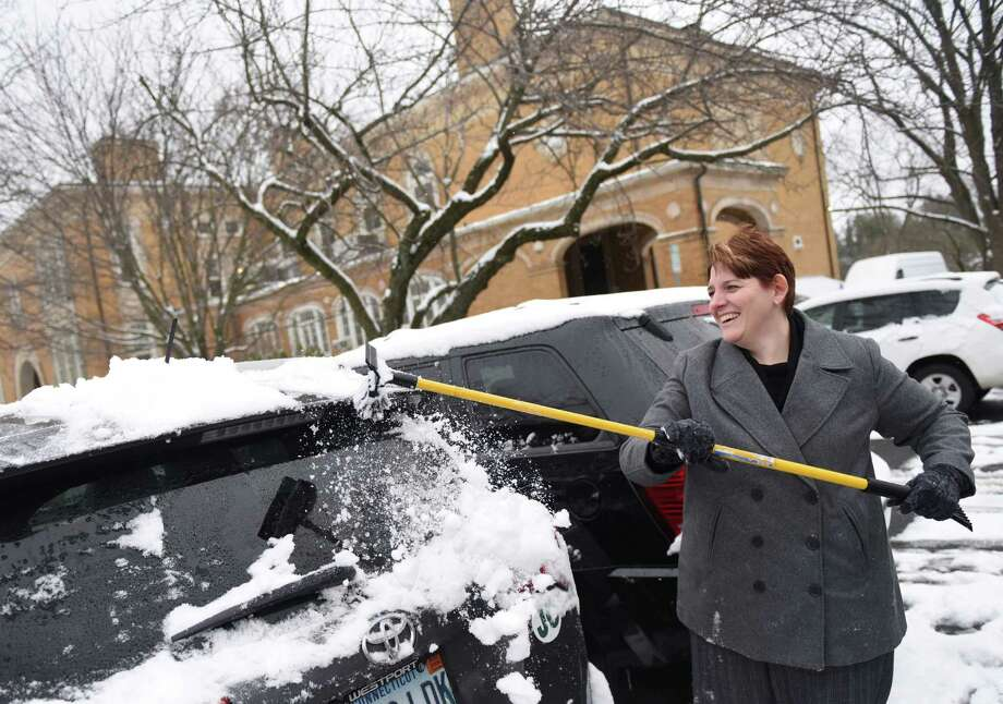 Julian Curtiss School Asst. Principal Brenda Brush cleans snow off her car outside the Board of Education building in Greenwich, Conn. Monday, Feb. 8, 2016. Greenwich received consistent light snow Monday with temperatures around 30 degrees and more light snow is expected Tuesday. Photo: Tyler Sizemore, Hearst Connecticut Media / Greenwich Time