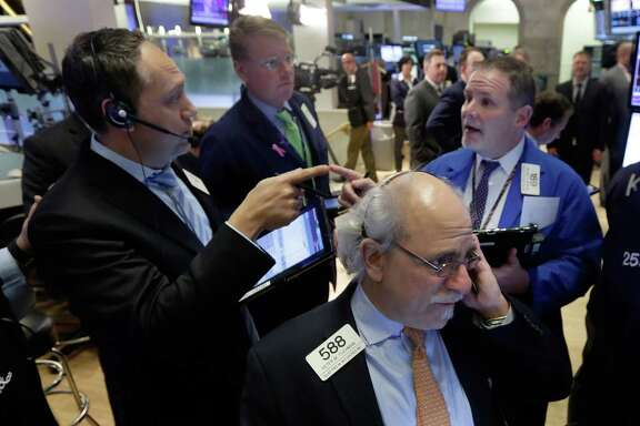 Traders work on the floor of the New York Stock Exchange on Monday. Investors unloaded materials, financials and other stocks, briefly knocking the Dow Jones industrial average down more than 400 points before a late-afternoon rally regained some of the losses.
