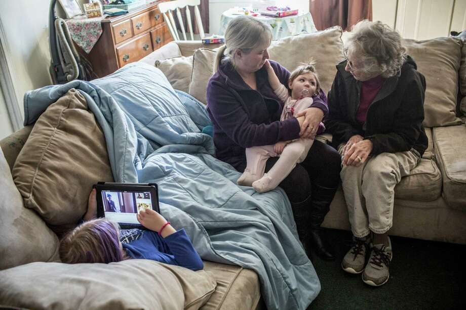 Alainah Therrien, diagnosed with microcephaly, rests in grandmother Heather Crossman's lap, near great-grandmother Rosalie Wherity. Photo: Shiho Fukada /New York Times / NYTNS