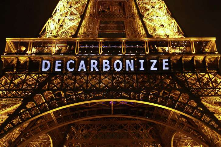 """The slogan """"DECARBONIZE"""" is projected on the Eiffel Tower as part of the COP21, United Nations Climate Change Conference in Paris, France, Friday, Dec. 11, 2015. (AP Photo/Francois Mori)"""