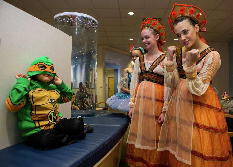 Kevin Bolton II puts a Ninja Turtle mask on as he is greeted by Katy Harvey, center, and Emily Seymour as members of Houston Ballet's production of The Sleeping Beauty make a special visit to patients Texas Children's Cancer and Hematology Centers on Monday, Feb. 8, 2016, in Houston. Photo: Brett Coomer, Houston Chronicle / © 2016 Houston Chronicle