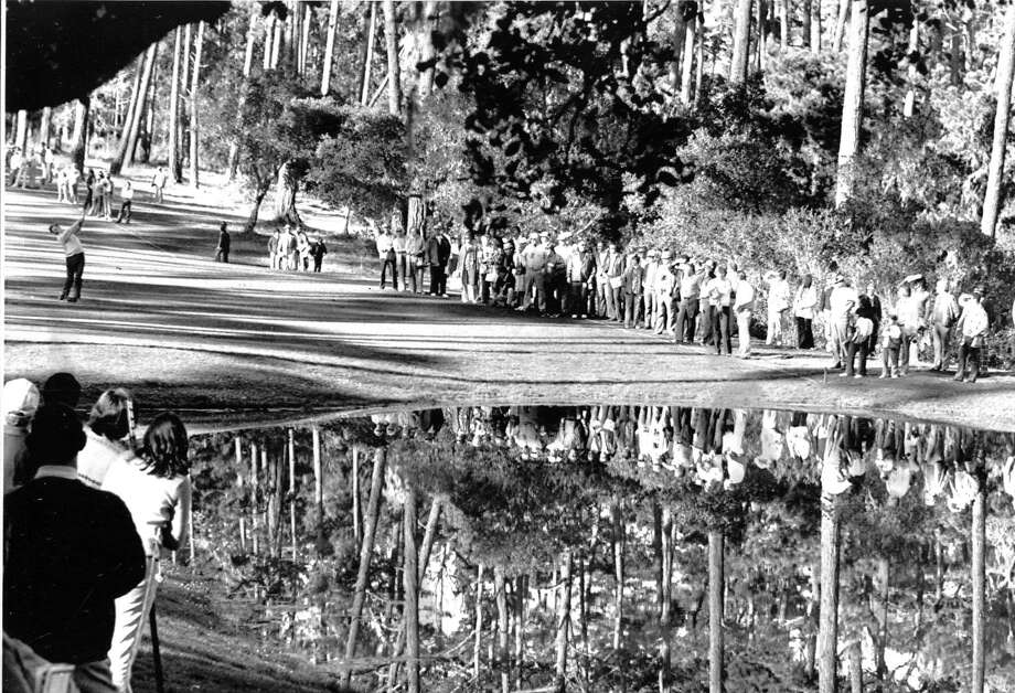 Actor George C. Scott and the gallery are reflected in the pond at the 1975 Crosby National Pro-Am Golf Tournament.