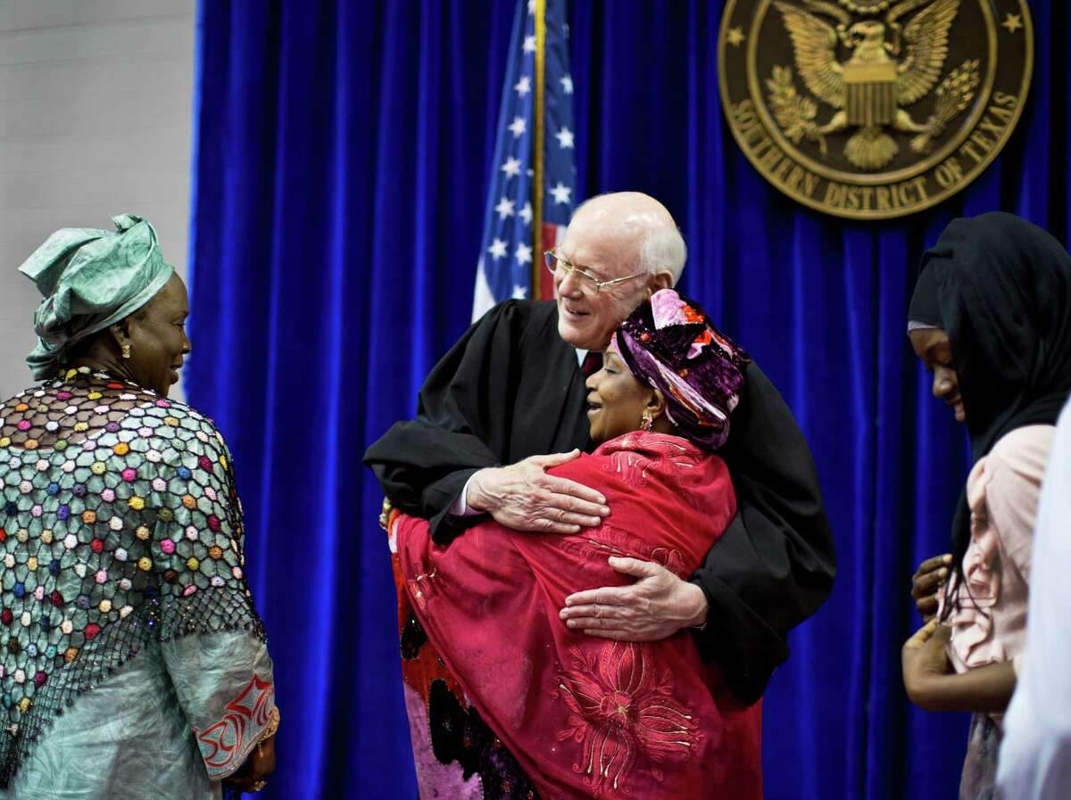 U.S. District Judge Lynn N. Hughes embraces Djene Kaba Traore at a naturalization ceremony in 2014.