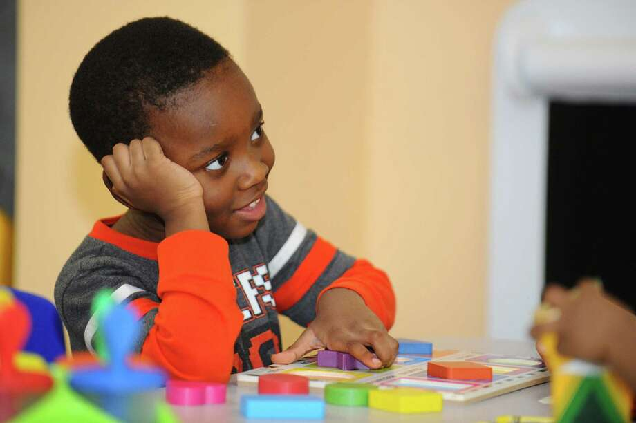 Three- year old Amar'e Marcilous plays with a shapes puzzle. Photo: Michael Cummo / Hearst Connecticut Media / Stamford Advocate