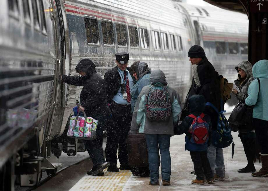 Amtrak passengers board a southbound train in swirling snow Monday, Feb. 8, 2016 at Union Station in New London, Conn. (Sean D. Elliot(/The Day via AP)  ORG XMIT: CTNLD103 Photo: Sean D. Elliot / The Day