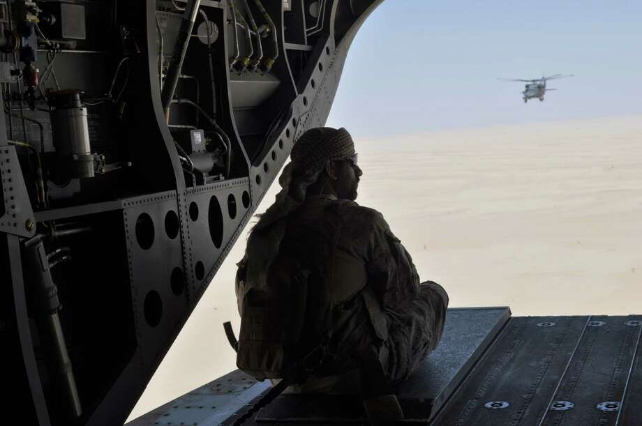 FILE- In this Monday, Sept. 14, 2015 file photo, an Emirati soldier stands guard out the rear gate of a Chinook military helicopter, escorted by a Blackhawk helicopter, traveling from Saudi Arabia to Yemen. Saudi Arabia's offer to put boots on the ground to fight Islamic State in Syria is as much about the kingdom's growing determination to flex its military might as it is about answering U.S. calls for more help from Mideast allies. (AP Photo/Adam Schreck, file) ORG XMIT: ARE102 Photo: Adam Schreck / AP