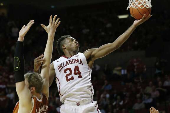 Oklahoma guard Buddy Hield (24) shoots behind Texas forward Connor Lammert, left, in the second half of an NCAA college basketball game in Norman, Okla., Monday, Feb. 8, 2016. Oklahoma won 63-60. (AP Photo/Sue Ogrocki)