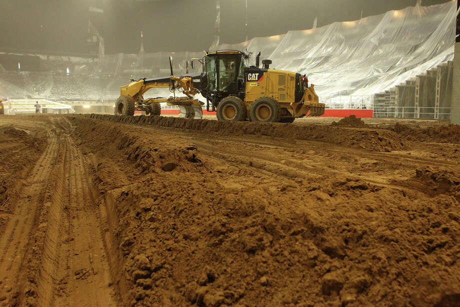 A grader operator spreads dirt in the AT&T Center in preparation for the rodeo, which opens Thursday. Photo: Photos By John Davenport /San Antonio Express-News / ©San Antonio Express-News/John Davenport