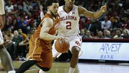 Texas guard Javan Felix, left, drives around Oklahoma guard Dinjiyl Walker (2) in the first half of an NCAA college basketball game in Norman, Okla., Monday, Feb. 8, 2016. (AP Photo/Sue Ogrocki)