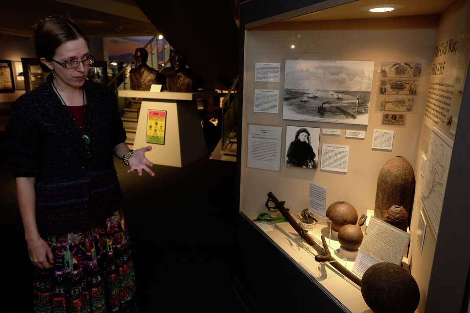 Sarah Bellian, curator at the Museum of the Gulf Coast, talks about a display of museum's Civil War memorabilia, including cannonballs and the bill of sale for a 17-year-old female slave named Nancy.  Photo taken Monday, February 08, 2016 Ryan Pelham/The Enterprise