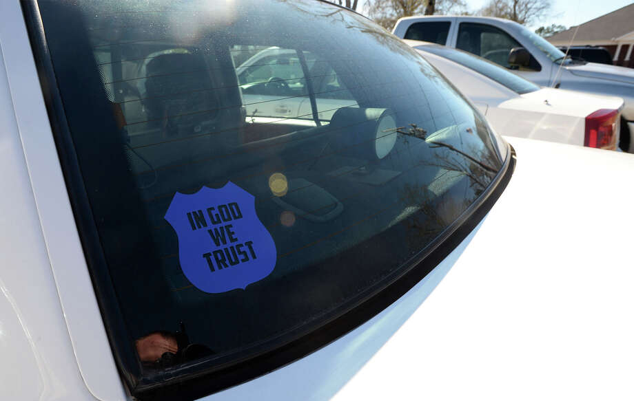"The Orange City Council unanimously approved Monday the placement of the phrase ""In God We Trust"" on city-owned vehicles. Some Kountze patrol cars, pictured, now have religious decals posted on the windows. 
