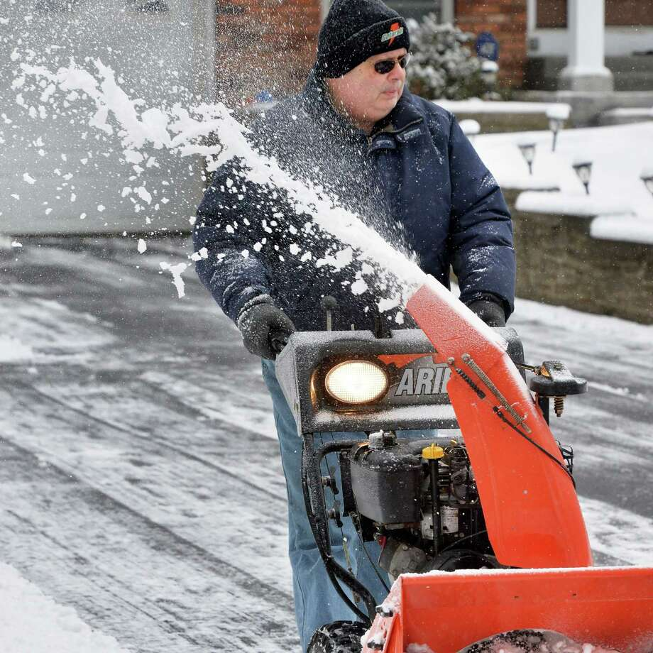 His own driveway cleared, David Cianciola snow blows his neighbor's driveway Tuesday Feb. 9, 2016 in Clifton Park, NY.  (John Carl D'Annibale / Times Union) Photo: John Carl D'Annibale / 10035338A