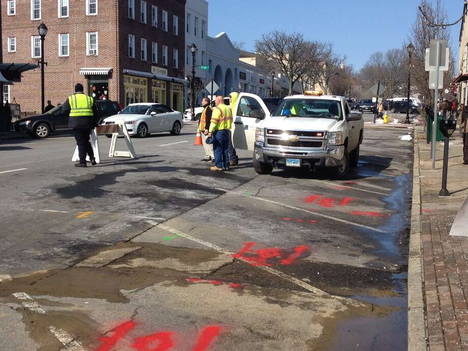 A dozen parking spaces were blocked off while workers fixed a broken water line on lower Greenwich Avenue. Photo: / Robert Marchant / Hearst Media