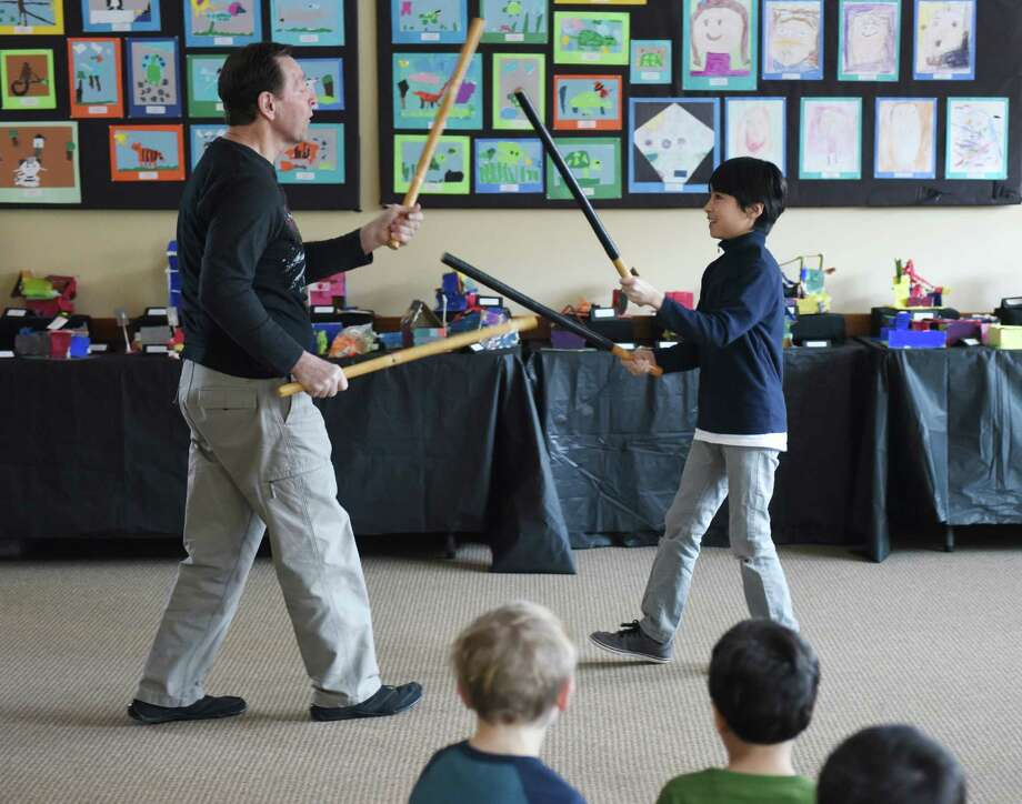 Instructor Ken Dolan and Zacharia Harrim, 5, of Pemberwick, participate in a Tai Chi routine using sticks during the Star Wars Tai Chi class at Byram Shubert Library in Greenwich, Conn. Tuesday, Feb. 9, 2016. Set to music from Star Wars, students learned the art of Tai Chi, which is said to improve balance, concentration, flexibility, focus, attention and learning. The Byram Shubert Library has a variety of activities for students' February vacation break, continuing Wednesday with a Young Hercules puppet show and R.E.A.D. to a Dog, and Thursday with a puppet-building workshop and musical performance by The Frank Porto Band. Photo: Tyler Sizemore, Hearst Connecticut Media / Greenwich Time