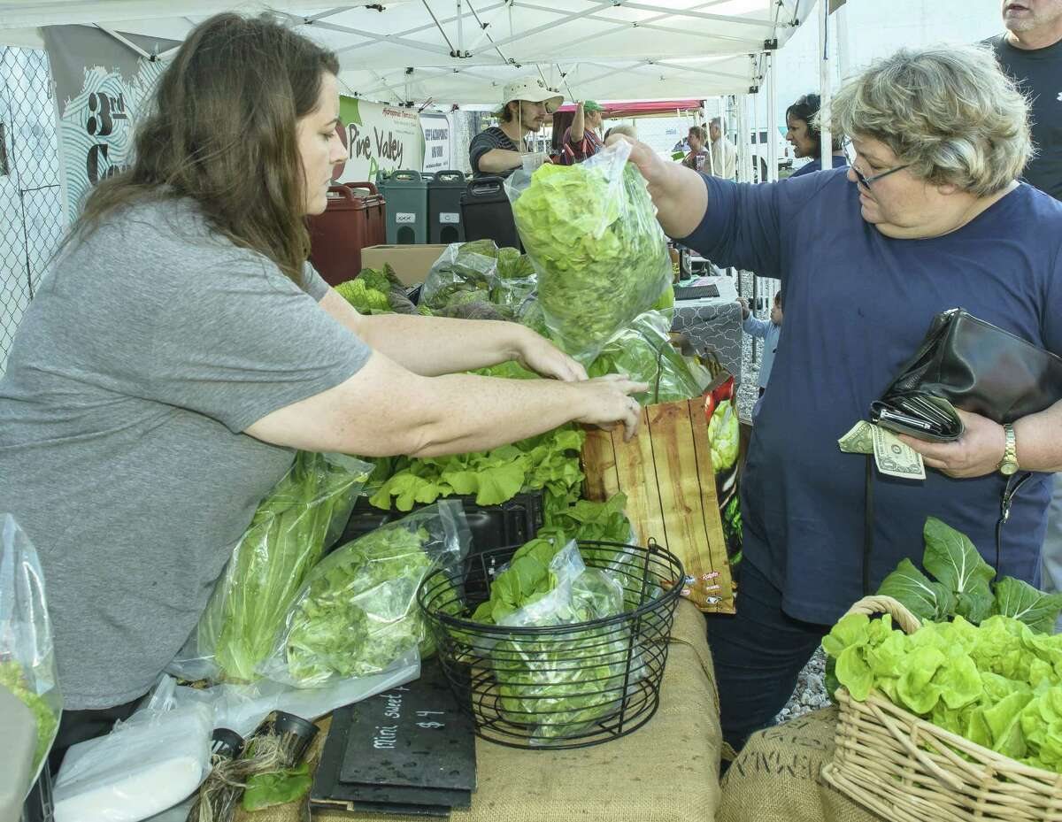 Heidi Hall with Island Aquaponics sells some of her vegetables to Cathy McLean of Galveston at the Galveston Farmers Market, which opened in 2012.