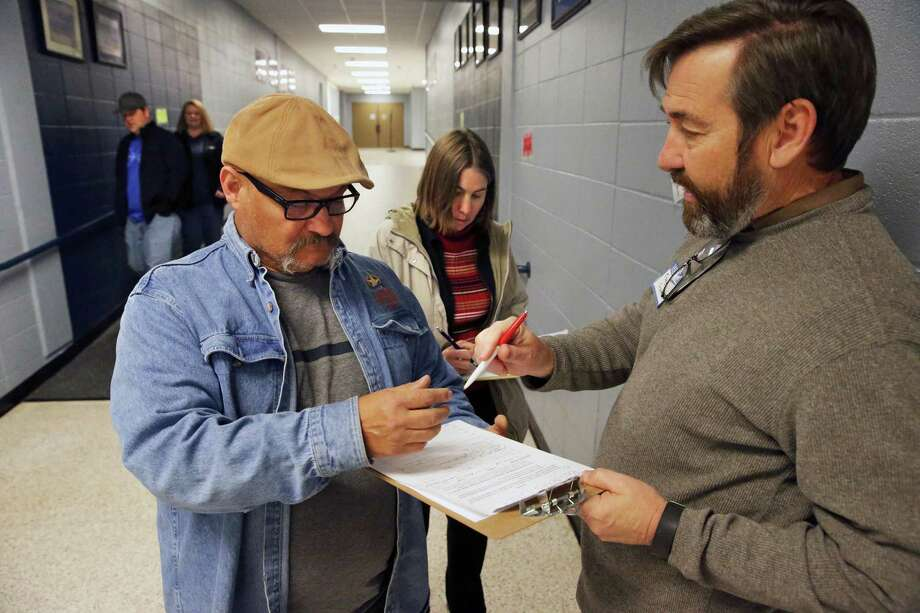 Tracy Crane (right) gets Bonifacio Lara and Rebecca Velez to sign a petition as citizens of the Oak Run subdivision gather for a town hall meeting with New Braunfels ISD and local government officials on February 4, 2016 at Oak Run Middle School concerning the proposed construction of a roadway through their neighborhood into the site of a new elementary school in the Veramendi development on the outskirts of town. Photo: TOM REEL, STAFF / SAN ANTONIO EXPRESS-NEWS / 2016 SAN ANTONIO EXPRESS-NEWS