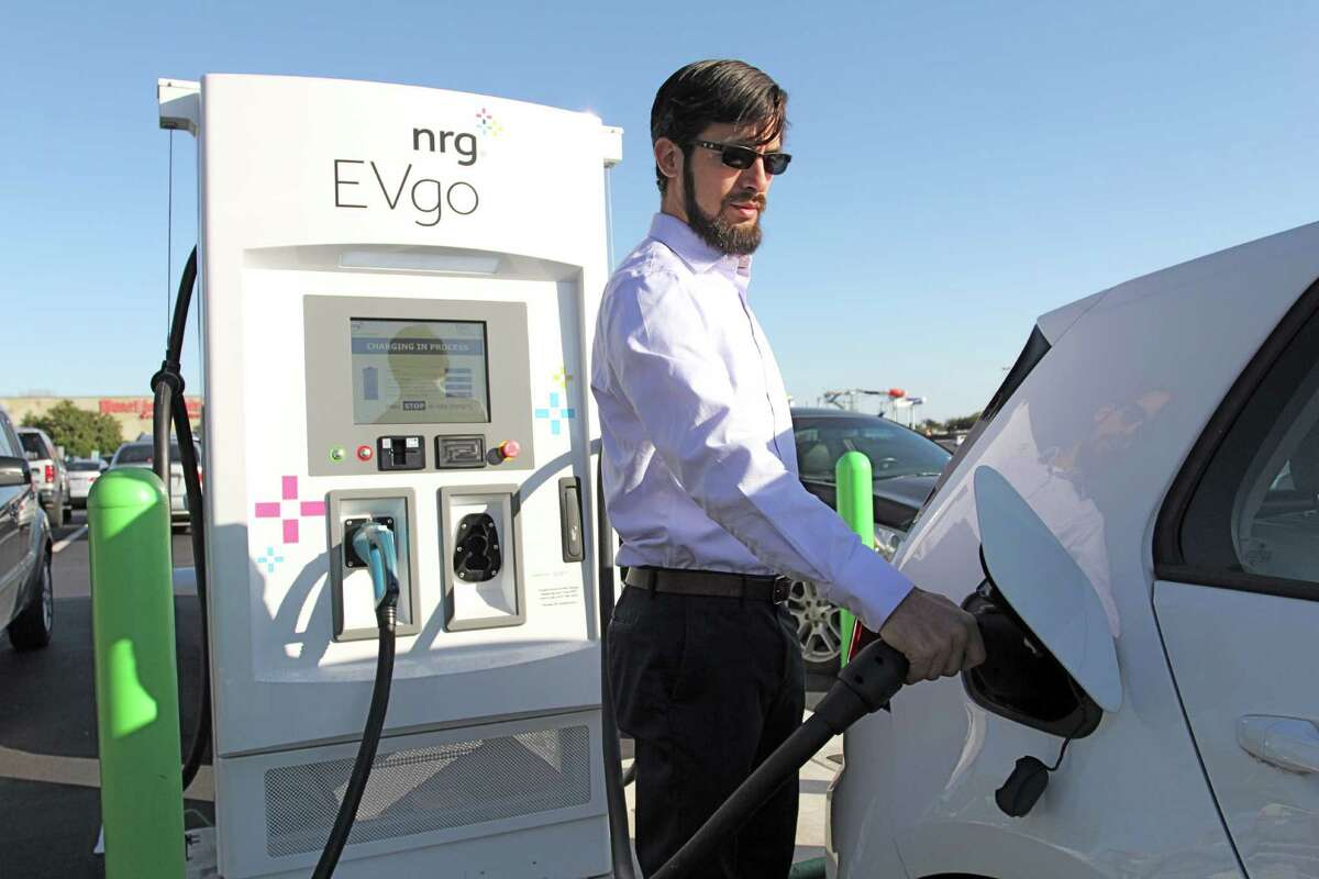 Anthony Martinez, equipment engineer for NRG, charges a VW e-Golf, a company vehicle, at the new EVgo electric charging station in the Katy Mills Mall parking lot outside Bed Bath & Beyond. The station and another existing one at the mall can together handle all types of electric vehicles.
