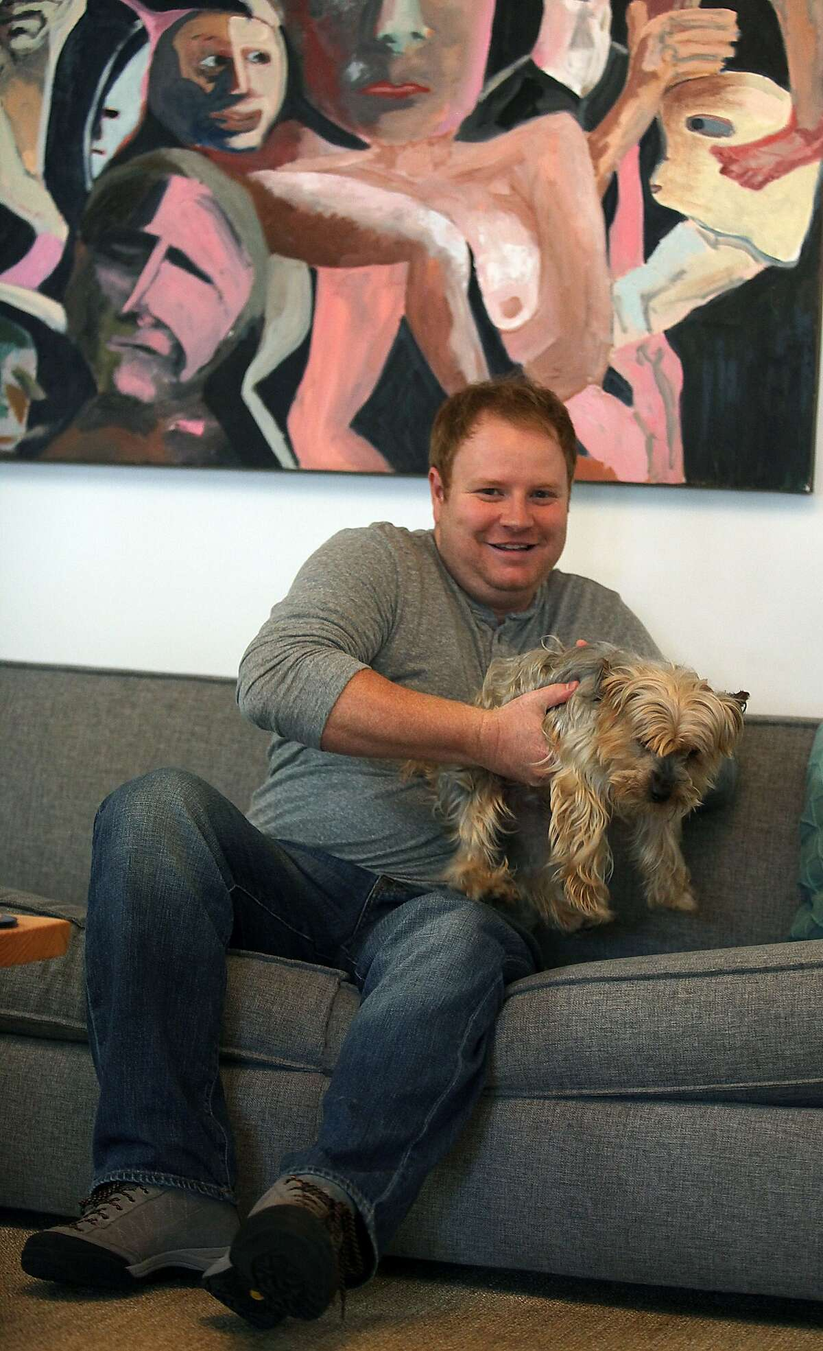 Zenefits CEO Parker Conrad plays with his dog Ajax in front of his dad's painting at his office in San Francisco, Calif., on Friday, November 7, 2014.