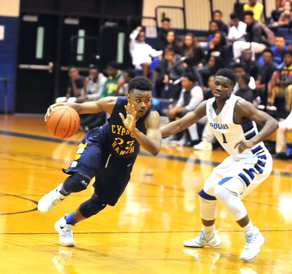 Cy Ranch's Michael Tate (23), left, drives past Cy Creek's Davon Berry in the Mustangs' 56-43 win.