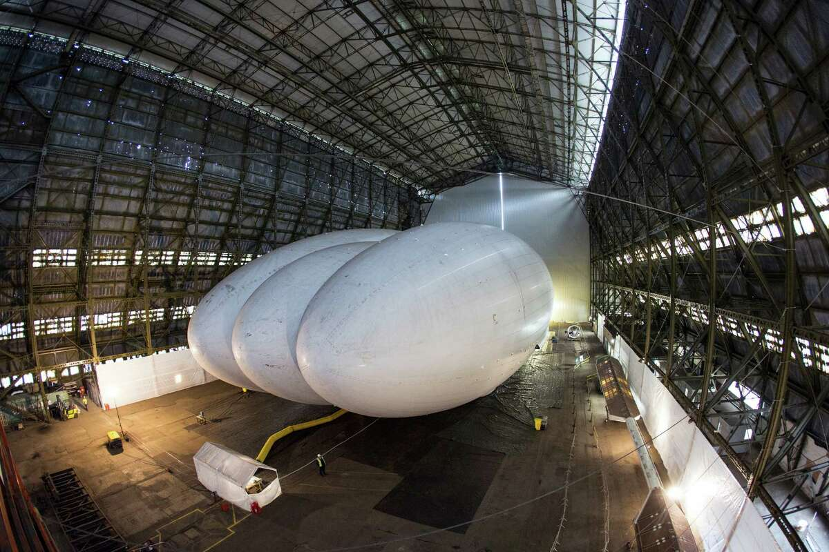 Mike Durham, the Technical Director at Hybrid Air Vehicles, admires the helium-filled 'Airlander' aircraft in a giant airship shed on February 28, 2014 in Cardington, England. The Airlander, which was originally developed for the US military before the project was cancelled due to budget cuts, is the world's longest aircraft at 92 meters. Although slow moving compared to conventional aircraft, the Airlander is able to carry large payloads over long distances very efficiently. Hybrid Air Vehicles' project to develop the technology further is being funded by a Government grant as well as private finance from individuals including Bruce Dickinson, the lead singer of the band Iron Maiden.