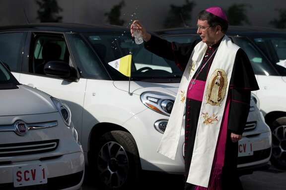 Papal Nuncio Christophe Pierre sprinkles holy water on the Fiat vehicles that will be used to transport Pope Francis during his visit to Mexico. In addition to the Fiats, five open-air popemobiles, built on Jeep and Dodge Ram frames, will be used for the visit.