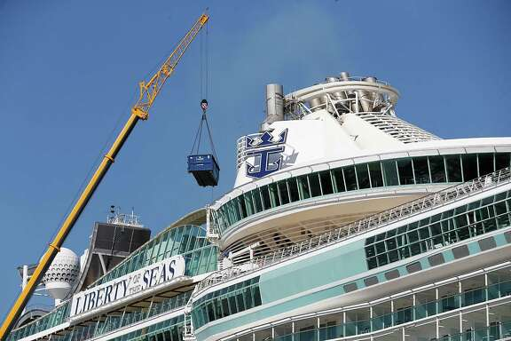 A crane loads cargo on the Royal Caribbean's Liberty of the Seas cruise ship as it sits in port on Sunday , February 7, 2016 in the Port of Galveston in  Galveston, Texas.