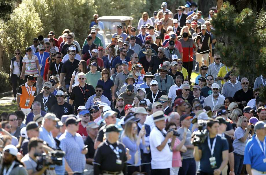 Crowds follow the first hole action, as teams from San Francisco Giants and the San Francisco 49ers square off in the Chevron Shoot-out for charity during the AT&T Pebble Beach Pro-Am, in Pebble Beach, California on Tues. February 9, 2016. Photo: Michael Macor