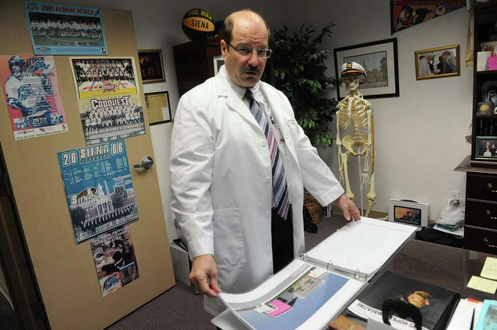 Dr. Joseph Marotta with architectural renderings of an orthopedic center he hopes to build in Ghana on Thursday Dec. 17, 2015 in Troy, N.Y. (Michael P. Farrell/Times Union)