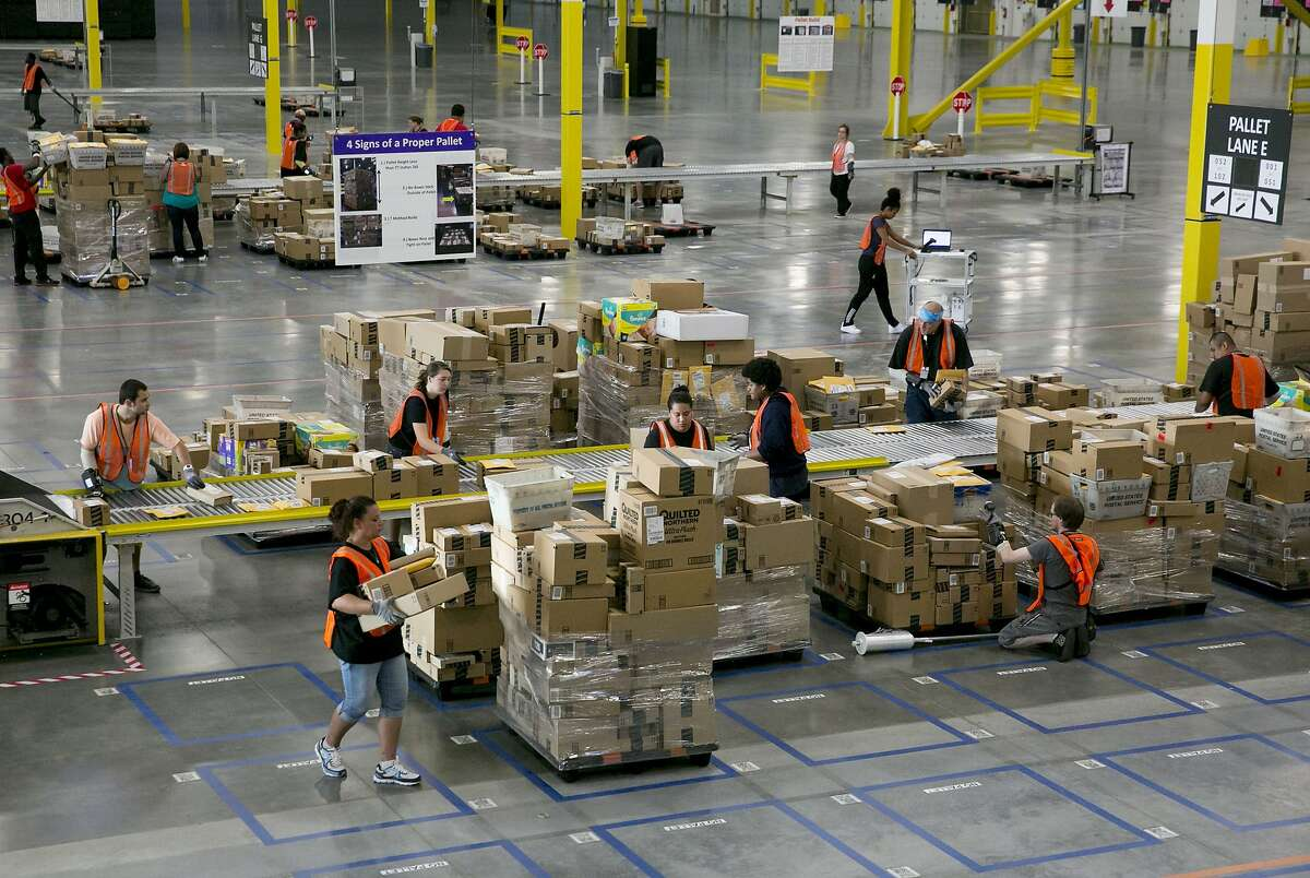 Employees work inside Amazon's 300,000-square-foot sorting center in Kent, Wa. The center allows Seattle-area residents to order some items as late as 11:59 p.m. and have them arrive the next day. (Erika Schultz/Seattle Times/TNS)