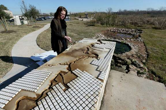 Anne Olson, president of the Buffalo Bayou Partnership, shows how bayou water will flow from a solar-powered cistern into wetlands at Buffalo Bend Nature Park.