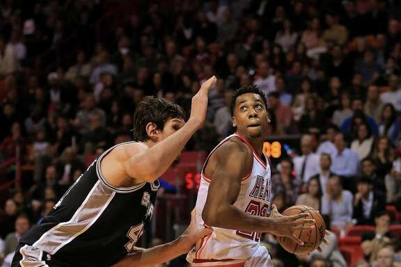 MIAMI, FL - FEBRUARY 09: Hassan Whiteside #21 of the Miami Heat drives on Boban Marjanovic #40 of the San Antonio Spurs during a game  at American Airlines Arena on February 9, 2016 in Miami, Florida. NOTE TO USER: User expressly acknowledges and agrees that, by downloading and/or using this photograph, user is consenting to the terms and conditions of the Getty Images License Agreement. Mandatory copyright notice: