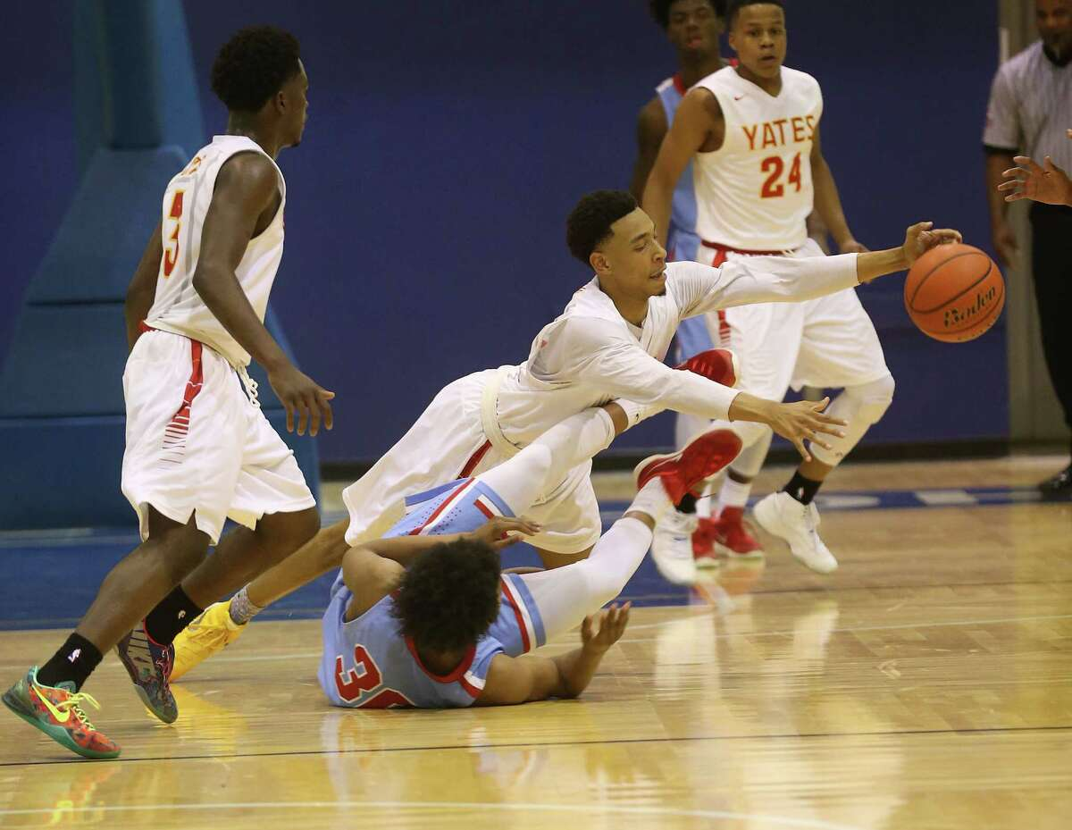 Yates' Maurice Hobson (0) dives for the ball over Madison's Chris Mayberry (30) to steal the ball in the second half of high school basketball action at Barnett Fieldhouse on Tuesday, Feb. 9, 2016, in Houston. Yates won the game 91-78.