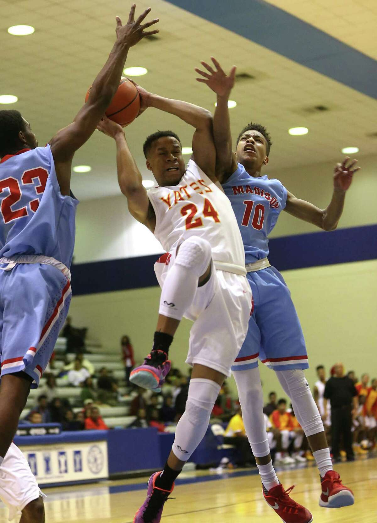 Yates' Jacob Young (24) cuts between Madison's Curtis Randle (23) and Jeremiah Gambrell (10) in the first half of high school basketball action between Yates and Madison at Barnett field house on Tuesday, Feb. 9, 2016, in Houston.