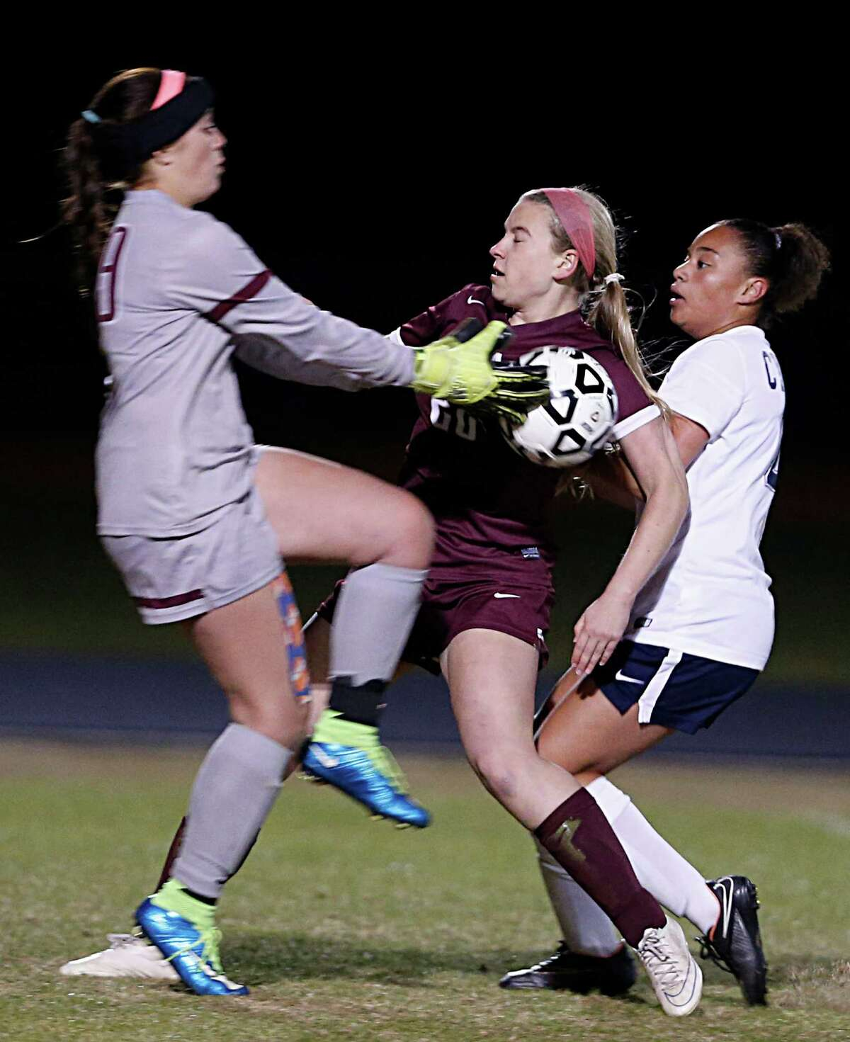 Cy-Fair's goal keeper Kennedy McGill left, blocks a shot as teammate Mackenzie Booth center, collides with Cy Ranch's Alyssa Austin right, during the second half of girls high school game action at Cypress Ranch High School Tuesday, Feb. 9, 2016, in Houston.