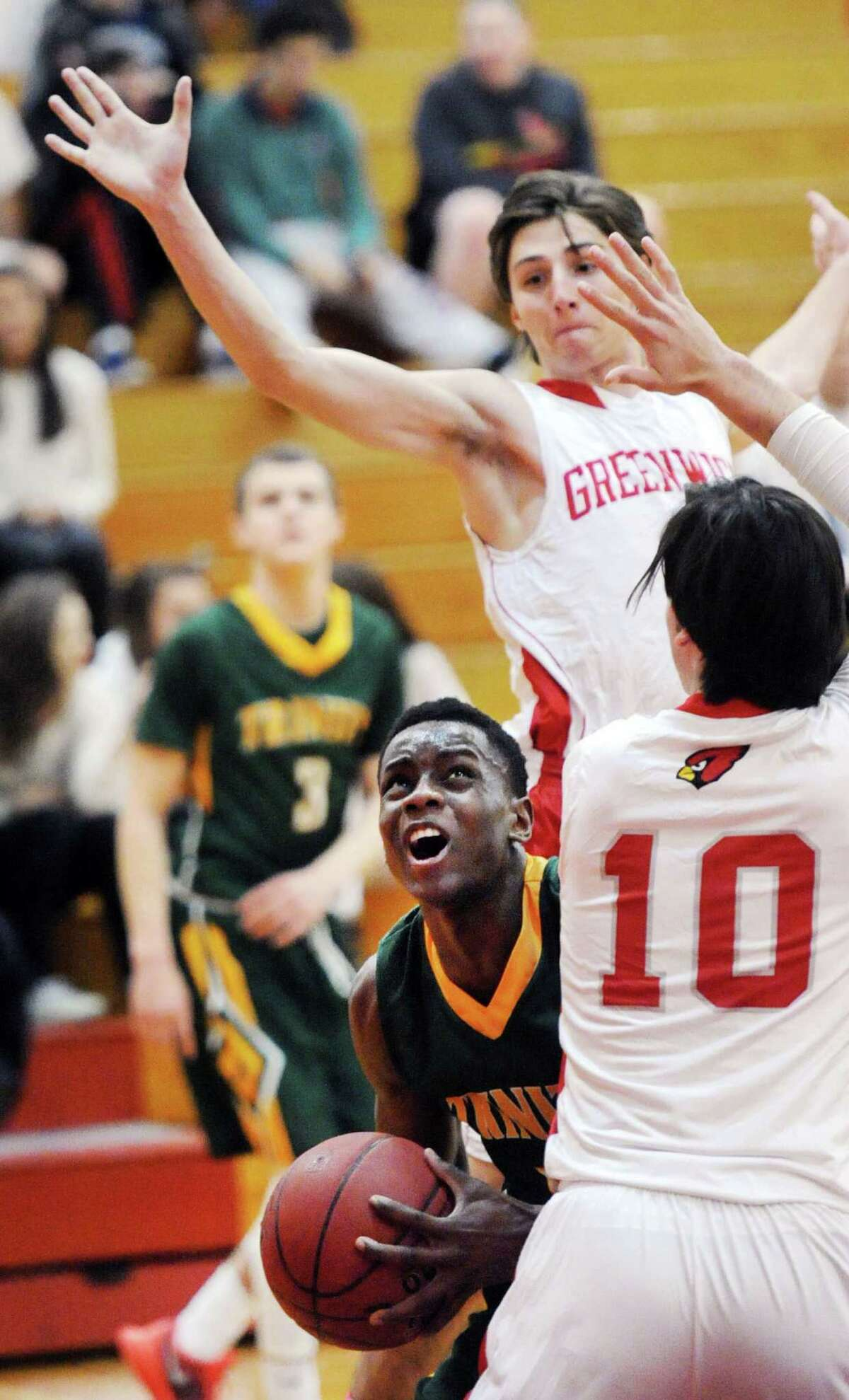 Trinity Catholic's Cantavio Dutreil, left, reacts as he pump-fakes a Greenwich defender in the air while getting around Connor Langan (10) on Tuesday night.