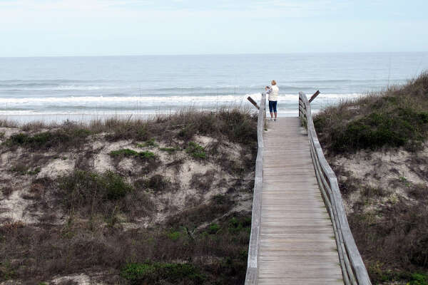In this Tuesday, Jan. 26, 2016 photo, a visitor takes a photo at once-segregated Butler Beach in St. Augustine, Fla. Now a public park, the beach was once set aside for blacks during the segregation era. Today it is a popular destination for families and other beachgoers, but there is no information posted at the site to inform visitors about its Jim Crow past. (AP Photo/Jason Dearen) ORG XMIT: NY670