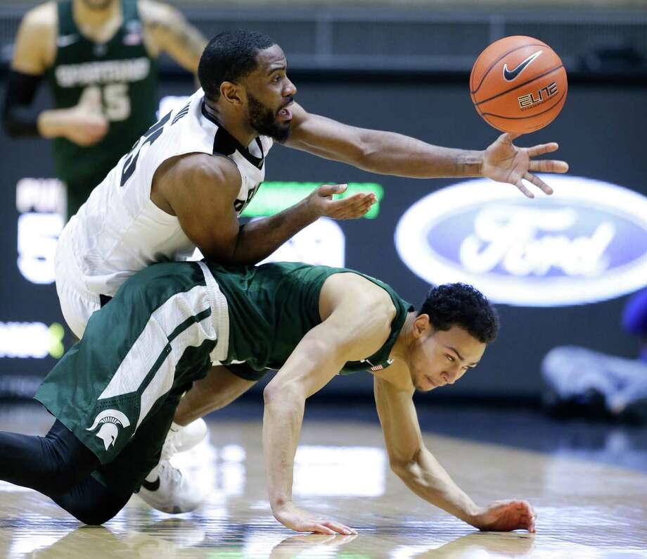 Purdue guard Rapheal Davis (35), top, attempts to pick up a loose ball over Michigan State guard Bryn Forbes (5) in the second half of an NCAA college basketball game in West Lafayette, Ind., Tuesday, Feb. 9, 2016. Purdue defeated Michigan State 82-81 in overtime. (AP Photo/Michael Conroy) ORG XMIT: INMC114 Photo: Michael Conroy / AP