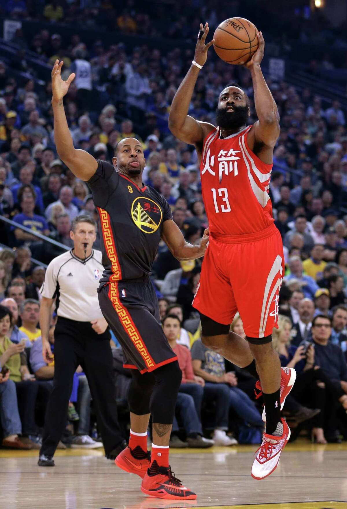 Houston Rockets' James Harden, right, shoots over Golden State Warriors' Andre Iguodala during the first half of an NBA basketball game Tuesday, Feb. 9, 2016, in Oakland, Calif. (AP Photo/Ben Margot)