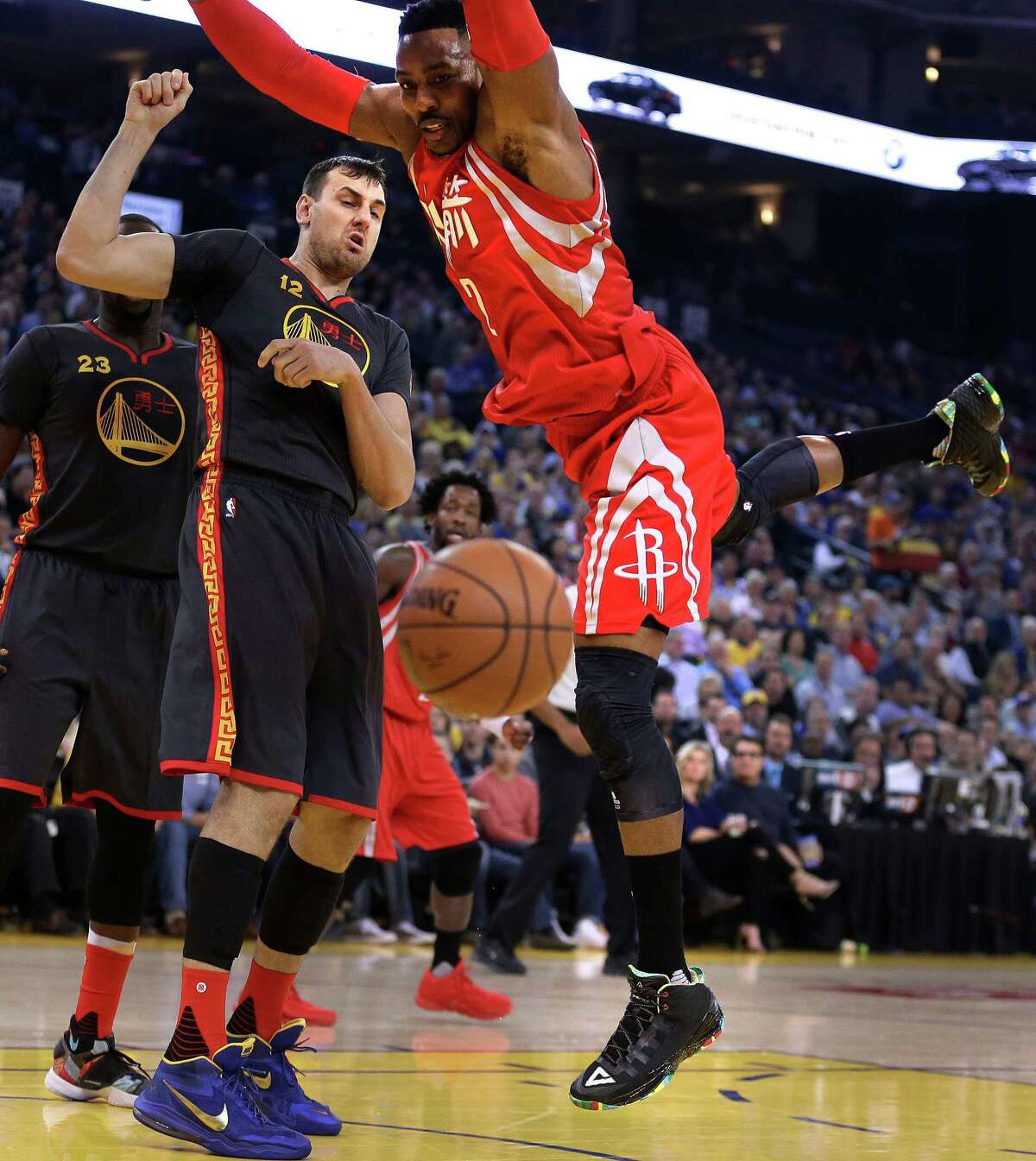 Golden State Warriors' Andrew Bogut (12) knocks the ball from Houston Rockets' Dwight Howard, right, during the first half of an NBA basketball game Tuesday, Feb. 9, 2016, in Oakland, Calif. (AP Photo/Ben Margot)