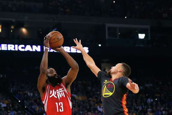 OAKLAND, CA - FEBRUARY 09:  James Harden #13 of the Houston Rockets shoots over Stephen Curry #30 of the Golden State Warriors at ORACLE Arena on February 9, 2016 in Oakland, California.  NOTE TO USER: User expressly acknowledges and agrees that, by downloading and or using this photograph, User is consenting to the terms and conditions of the Getty Images License Agreement.