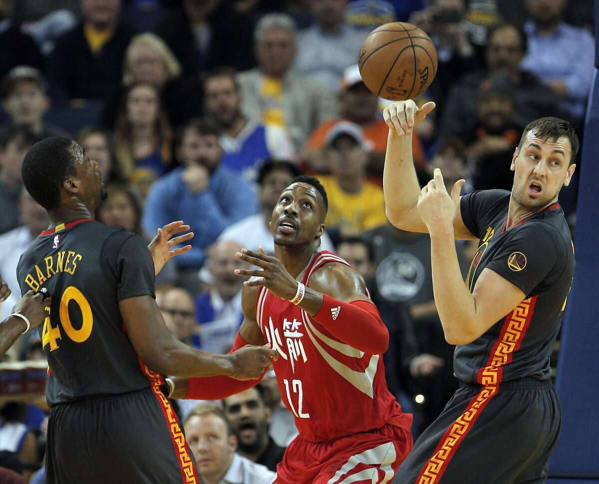 Andrew Bogut (12) bats away a rebound from Dwight Howard (12) during the first half of the game between the Golden State Warriors and the Houston Rockets at Oracle Arena in Oakland, Calif., on Tuesday, February 9, 2016.
