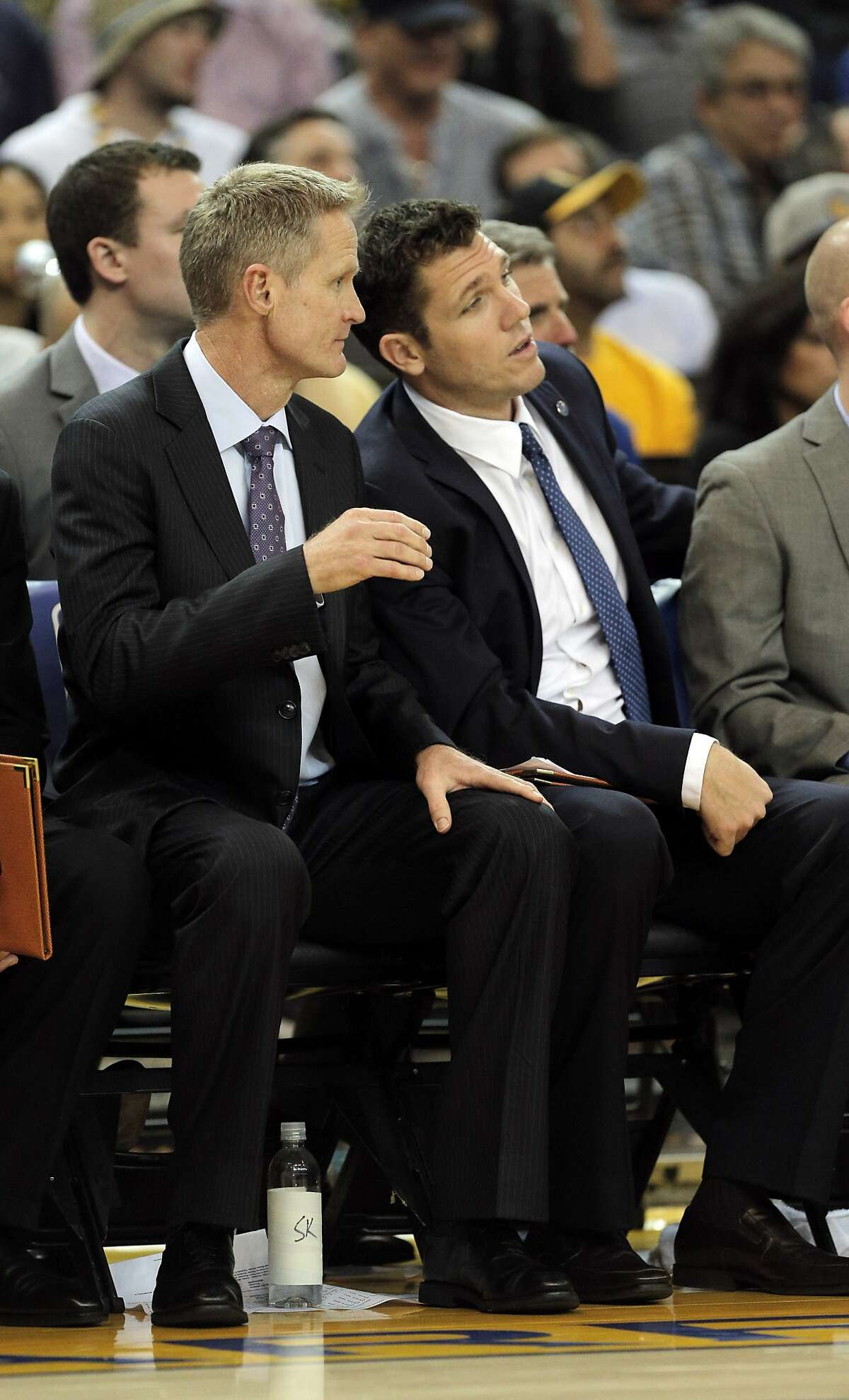 Head coach Steve Kerr, left, chats with assistant coach Luke Walton, right, during the first half of the game between the Golden State Warriors and the Houston Rockets at Oracle Arena in Oakland, Calif., on Tuesday, February 9, 2016.