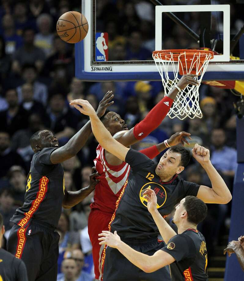 Draymond Green (23) and Andrew Bogut (12) battle against Dwight Howard (12) for a rebound during the first half of the game between the Golden State Warriors and the Houston Rockets at Oracle Arena in Oakland, Calif., on Tuesday, February 9, 2016. Photo: Carlos Avila Gonzalez, The Chronicle