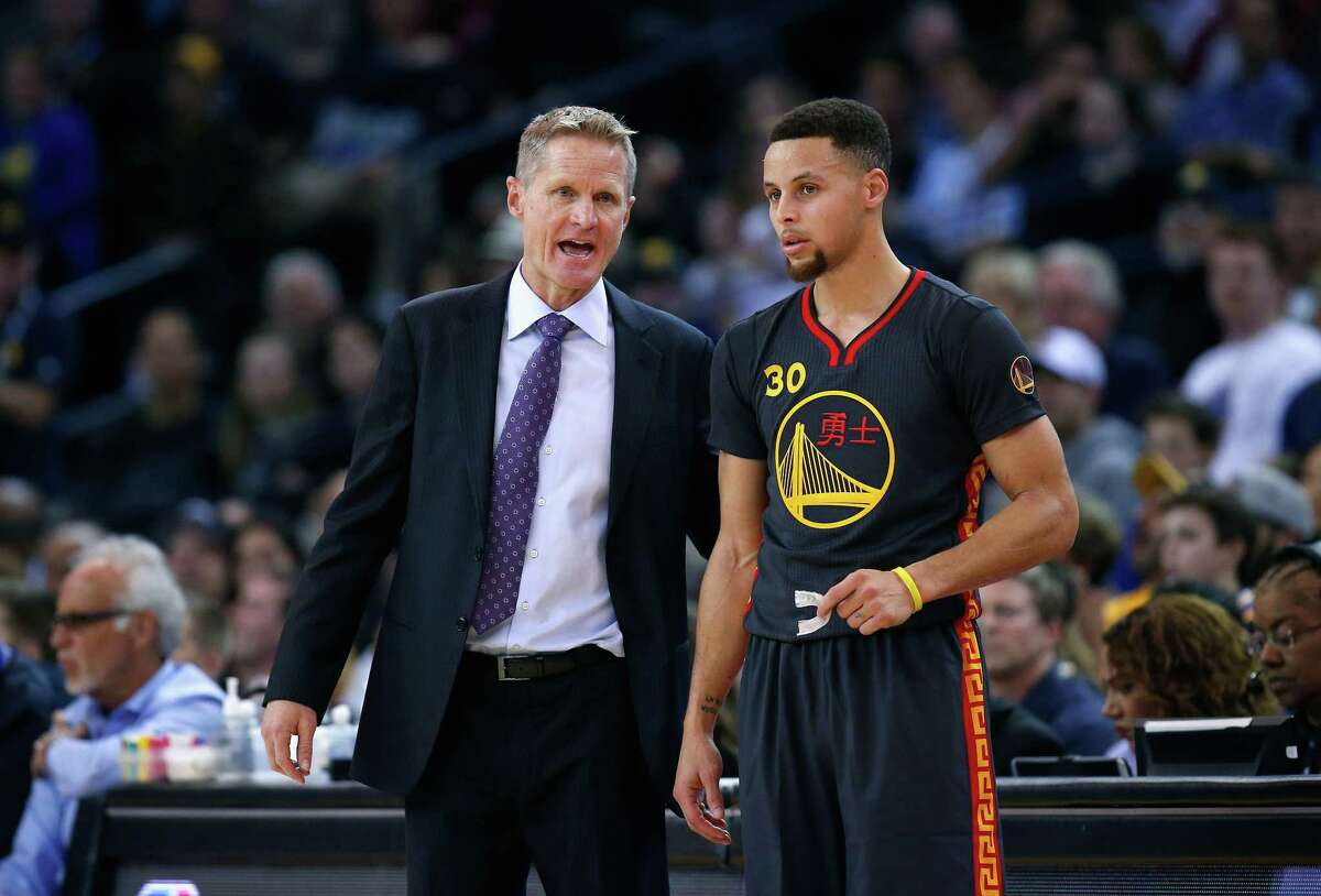 Head coach Steve Kerr of the Golden State Warriors talks to Stephen Curry #30 during their game against the Houston Rockets at ORACLE Arena on February 9, 2016 in Oakland, California.