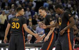 Stephen Curry (30) high fives Klay Thompson (11) and Harrison Barnes (40) during the second half of the game between the Golden State Warriors and the Houston Rockets at Oracle Arena in Oakland, Calif., on Tuesday, February 9, 2016.  The Warriors won 123-110.
